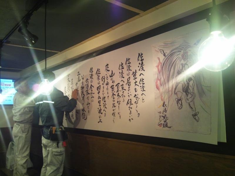 $「佐渡の酒と肴 だっちゃ」女店主きたむらさやかの営業日誌 東京メトロ浅草駅から徒歩20歩!-壁面の作品を取り付け中~。